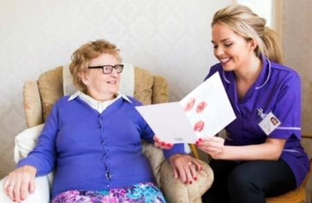 Carer looking at a booklet with an older lady