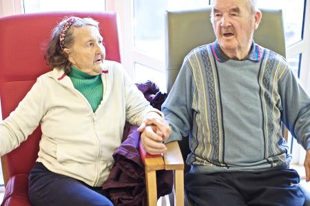 2 older people sitting in chairs in a room in a care home