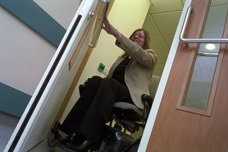 Woman in wheelchair coming through a door