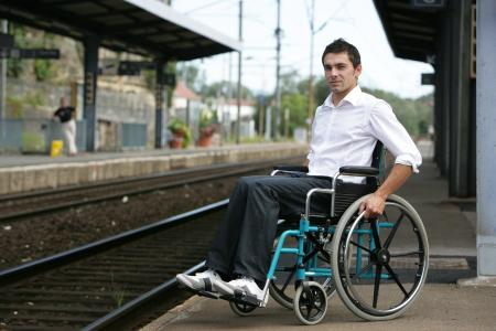 Young man in a wheelchair beside a train