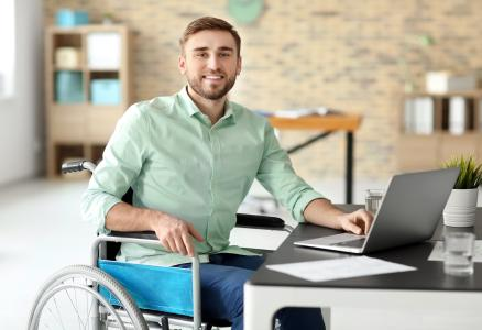 Young man in a wheelchair working at a computer