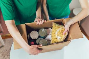 A picture of children making a food parcel box with tins and pasta