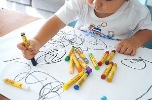 toddler drawing with crayons