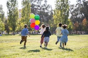 Children running colourful balloon