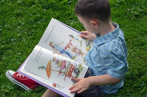 boy sitting on grass reading picture book