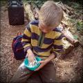 Child mixing Damper Bread to cook on the fire