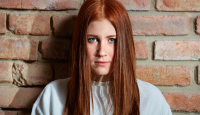 Girl with ginger hair standing with back to wall looking at the camera