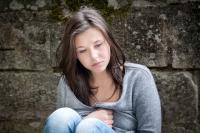 Image of a young teenage girl sitting looking down