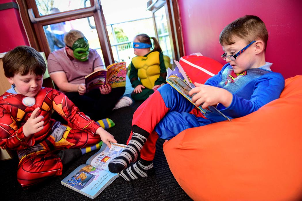 Children reading dressed as super heros