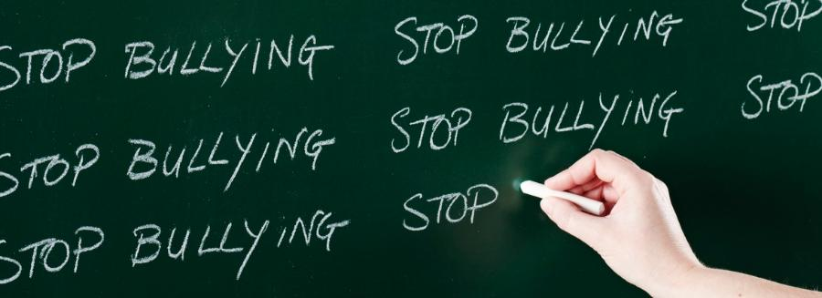Hand writing 'Stop bullying' on a chalkboard