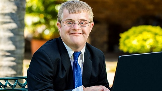 Smiling young man with Down's Syndrome in a suit with a laptop open