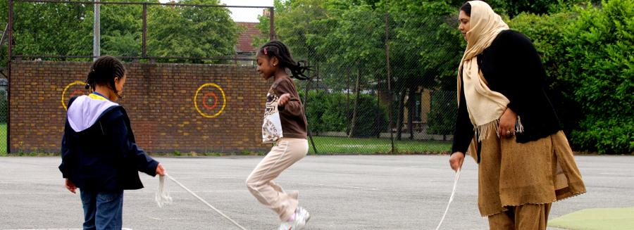 children skipping with childcare worker