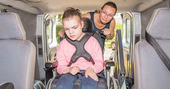 Girl in wheelchair being loaded into a vehicle