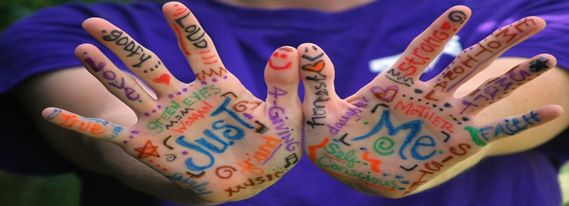 Hands outstretched with emotional and personal words covering palms and fingers in different colours