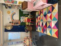 Colourful mat on floor with pink play kitchen