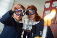 Two girls conducting a science experiment with goggles on