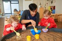 Childminder painting with two children