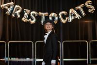 A girl on stage in a cat costume in front of a banner that says 'Aristocats'