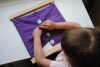 Child practicing to do up buttons