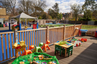 Outside play area with activities along a fence