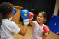 Two girls boxing with boxing gloves on