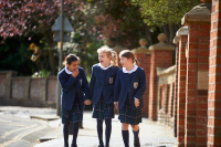 Three girls walking next to each other outside in school uniform