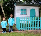 Two children standing next to a Wendy house with a blue picket fence