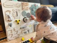 Child playing with an activity board with cogs and other things on it