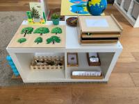 A small shelving unit with an activity in each section and on top