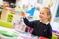 Child working at a table whilst smiling