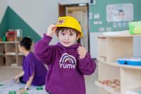 Child wearing yellow builders' hat