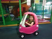 Young smiling girl in a play car, at an SEN relaxed session.