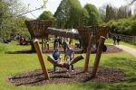 Two children sitting on log swing