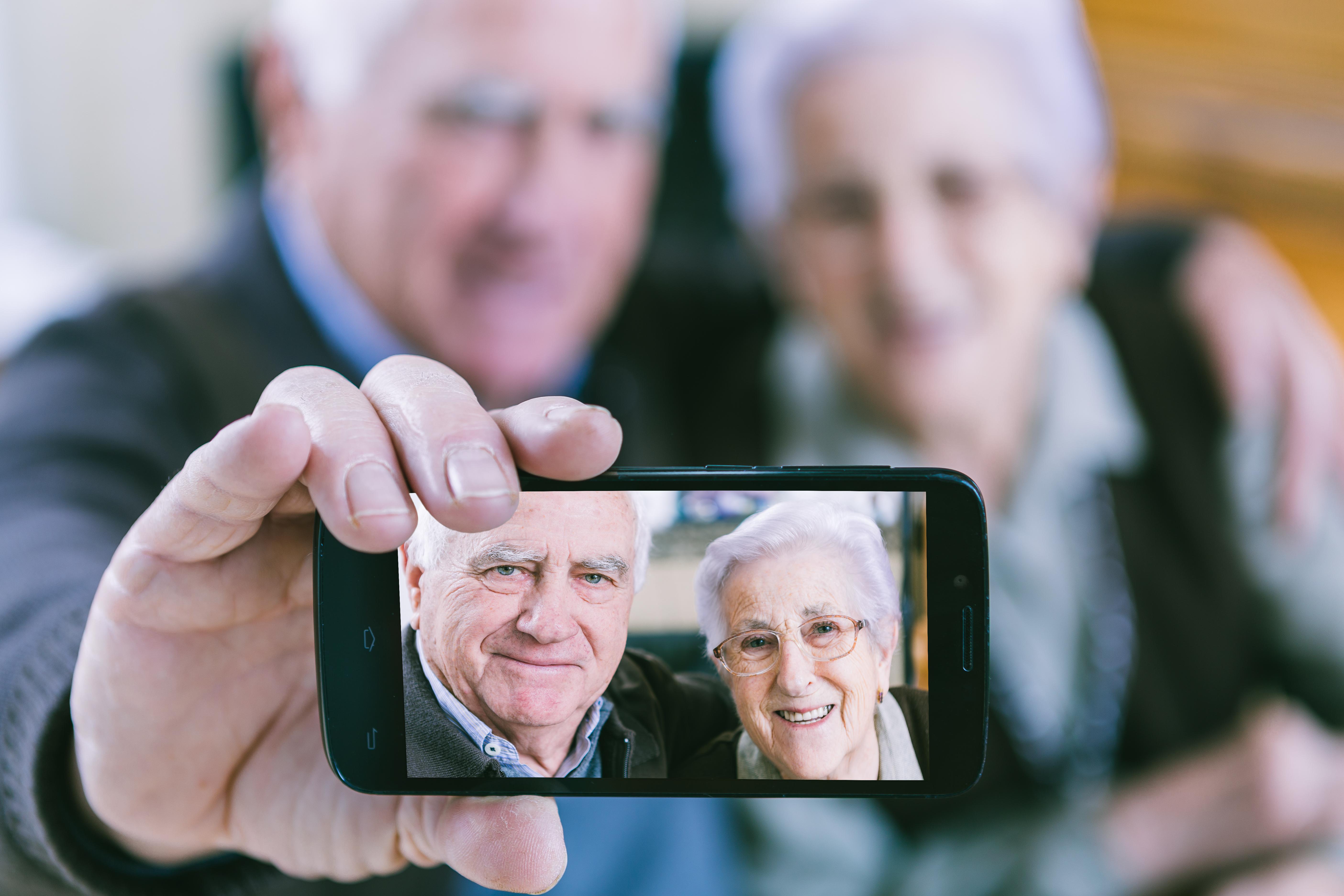 Two elderly people taking a selfie