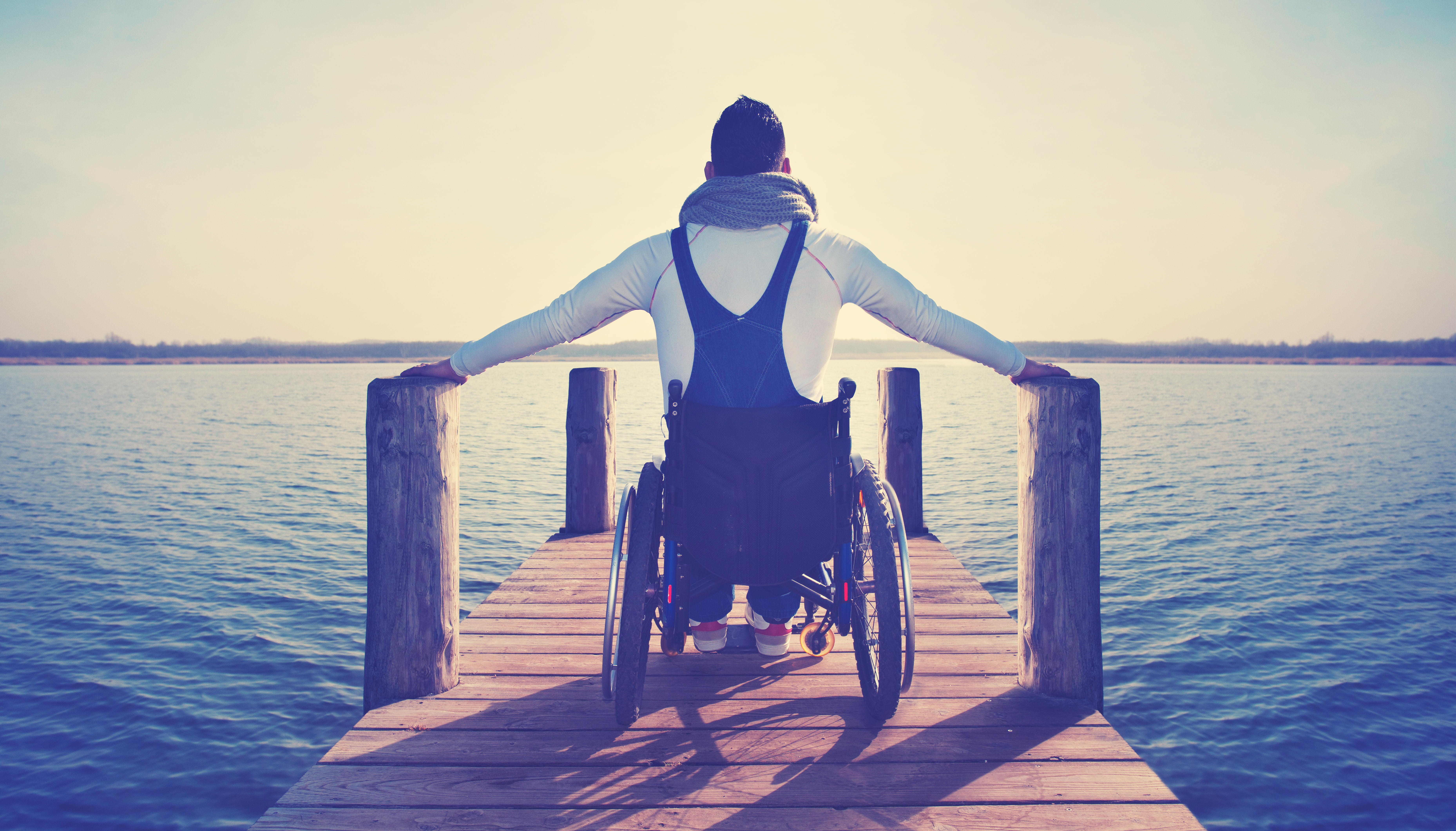 a man in a wheelchair looking out at a lake